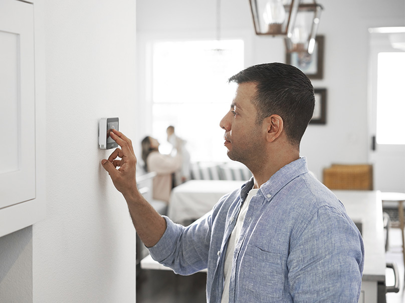 Man turning on thermostat